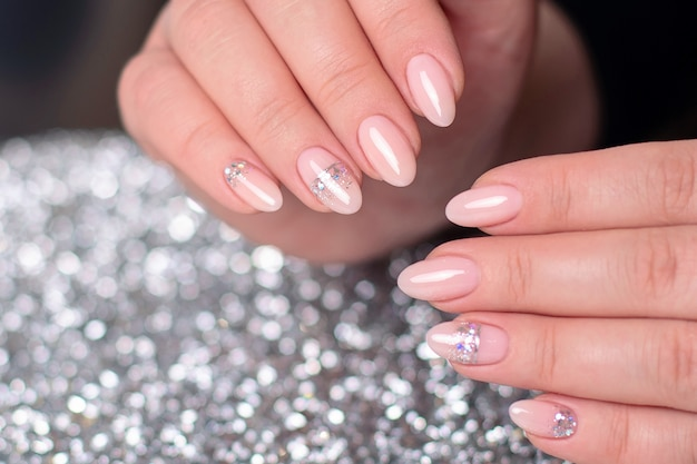 Mãos femininas com unhas de manicure românticas, esmalte de gel nude