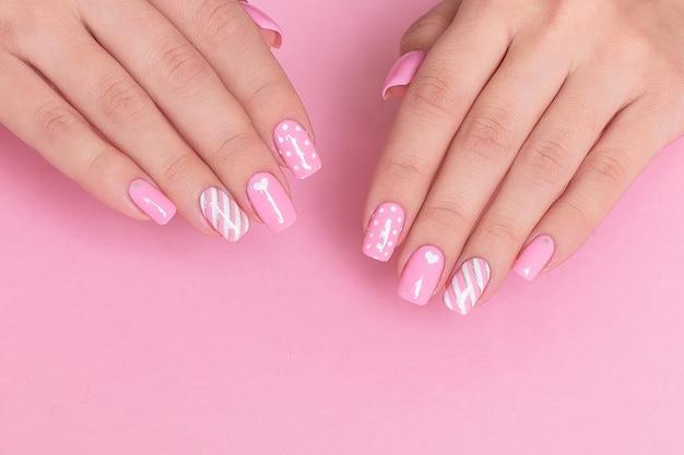 Mãos femininas com unhas de manicure rosa e design do dia dos namorados