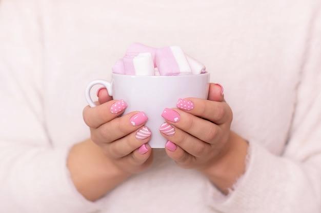 Mãos femininas com unhas de manicure rosa segurando uma xícara