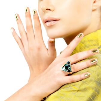 Mãos femininas com unhas douradas e esmeralda verde de pedra preciosa