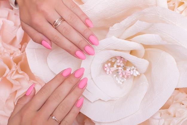 Mãos femininas com unhas rosa