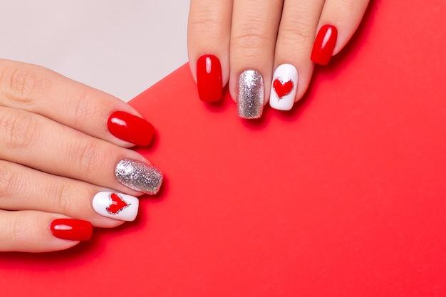Mãos femininas com unhas vermelhas de manicure