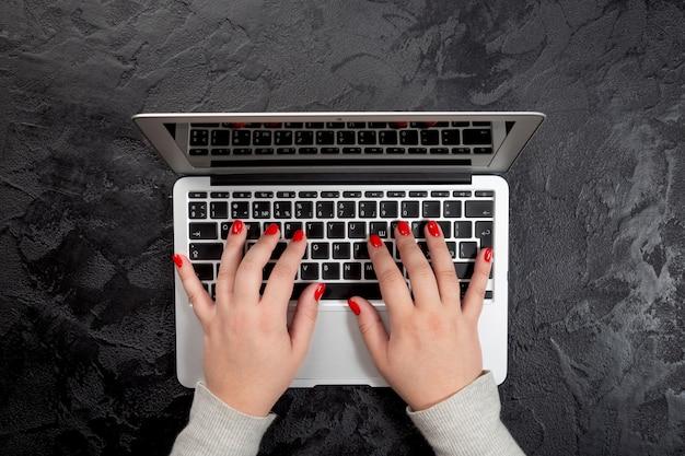 Mãos femininas com unhas vermelhas, digitando no laptop em fundo preto.