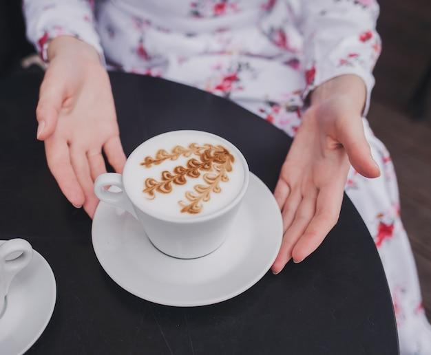 Mãos femininas com vestido segurando a xícara de café.