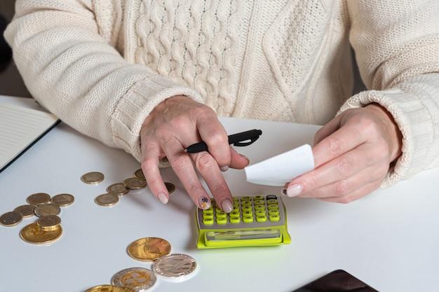 Mãos femininas contando dados, impostos de iva, custando a papelada na mesa do escritório em casa, close-up