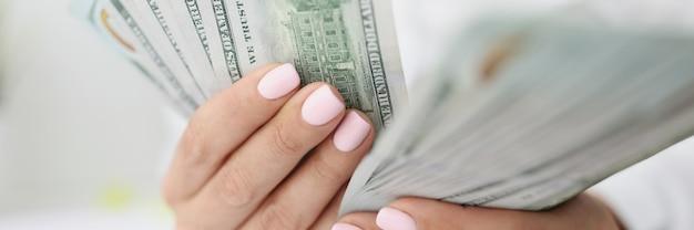 Mãos femininas contando notas de cem dólares americanos