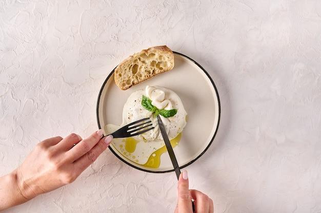 Mãos femininas cortadas com faca e garfo queijo burrata com óleo de manjericão e pão na vista superior do prato branco