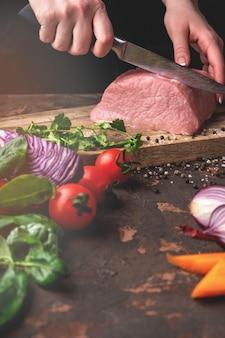 Mãos femininas cortam carne de porco crua em uma placa de madeira na cozinha, processo de cozimento de carne com legumes e especiarias
