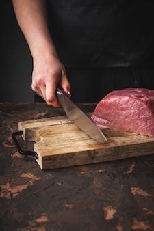 Mãos femininas cortam carne de porco crua em uma placa de madeira na cozinha