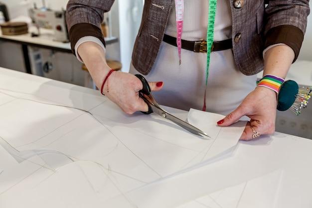 Mãos femininas cortam o padrão de papel com uma tesoura de alfaiate em uma mesa branca
