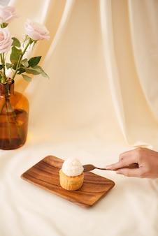 Mãos femininas cortam os deliciosos cupcakes na mesa