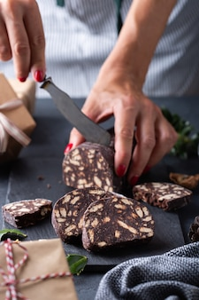 Mãos femininas cortando a tradicional sobremesa italiana, natal, chocolate, salame