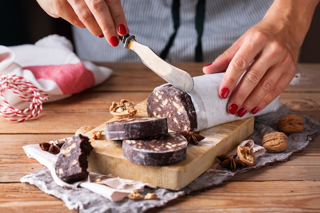 Mãos femininas cortando a tradicional sobremesa italiana - salame de chocolate de natal com biscoitos quebrados e nozes em uma mesa