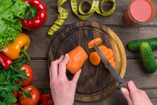 Mãos femininas cortando cenoura na mesa, vista superior. sobre a mesa folhas de alface, pimenta, um copo de suco de tomate, uma tábua de madeira e uma faca
