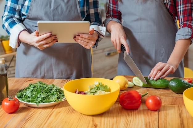 Mãos femininas cortando legumes na cozinha