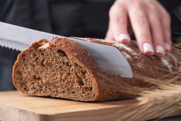 Mãos femininas cortando pão uma faca na placa de madeira. fechar-se