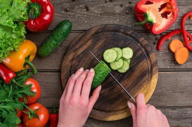 Mãos femininas cortando pepino na mesa, vista superior. sobre a mesa legumes e uma tábua de madeira