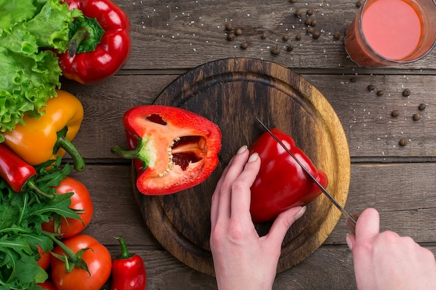 Mãos femininas cortando pimenta na mesa, vista superior. sobre a mesa folhas de alface, pimenta, um copo de suco de tomate, uma tábua de madeira e uma faca
