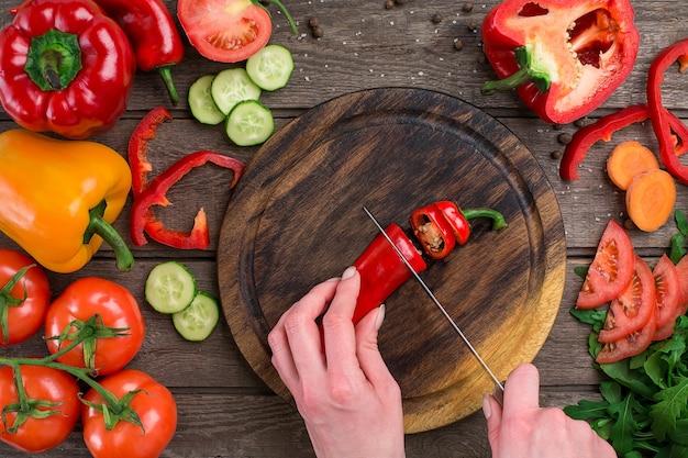 Mãos femininas cortando pimentas na mesa, vista superior. sobre a mesa legumes e uma tábua de madeira