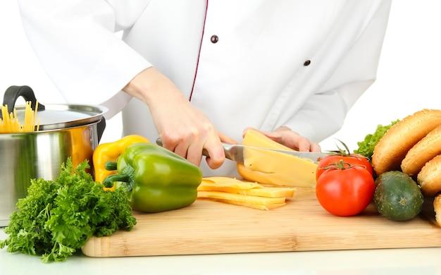 Mãos femininas cortando queijo, isolado no branco