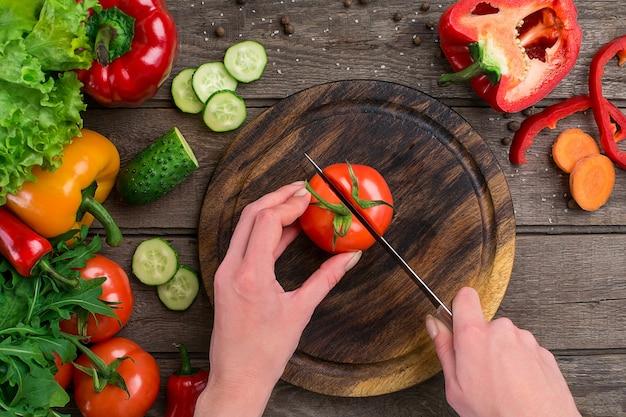 Mãos femininas cortando tomate na mesa, vista superior. sobre a mesa legumes e uma tábua de madeira