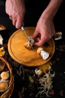 Mãos femininas cortar cogumelos em uma placa de cozinha