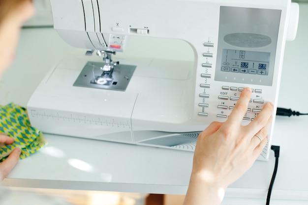 Mãos femininas costurando tecido branco em manufatura profissional