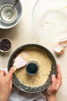 Mãos femininas cozinhando bolo em forma de lata de metal, massa crua para bolo