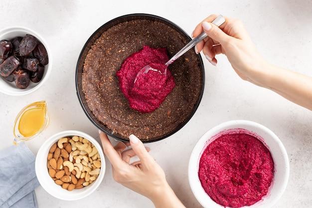 Mãos femininas cozinhando bolo vegetariano. comida alternativa saudável