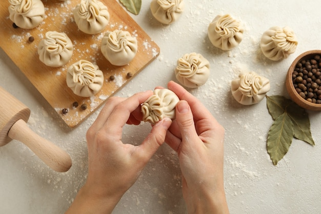 Mãos femininas cozinhando khinkali em fundo branco com ingredientes