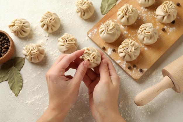 Mãos femininas cozinhando khinkali em uma mesa branca com ingredientes