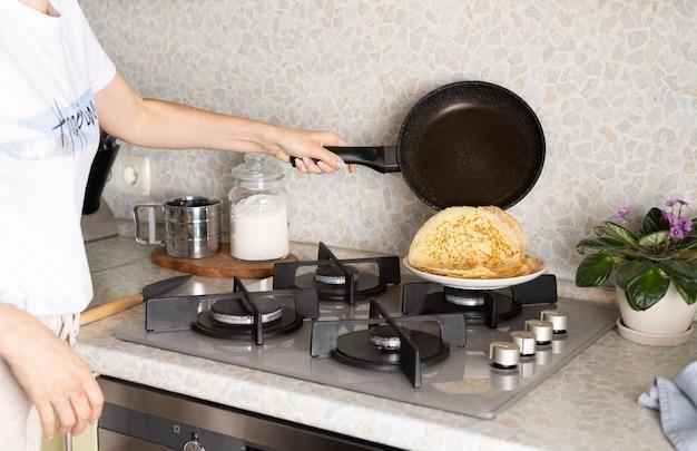 Mãos femininas cozinhando panquecas finas, crepes