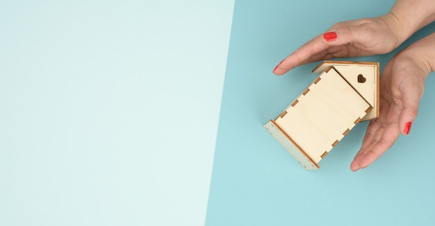 Mãos femininas cruzadas sobre uma casa modelo em miniatura de madeira sobre um fundo azul. conceito de seguro imobiliário, proteção ambiental, felicidade familiar