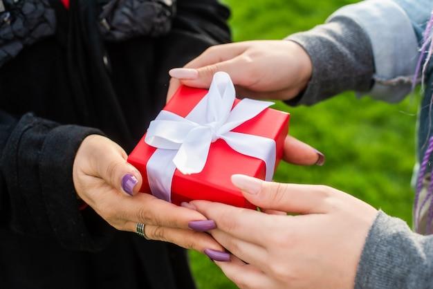 Mãos femininas dão um presente. dia das mães. mãe e filha. conceito de ano novo, natal, dia dos namorados. caixa vermelha com fita.