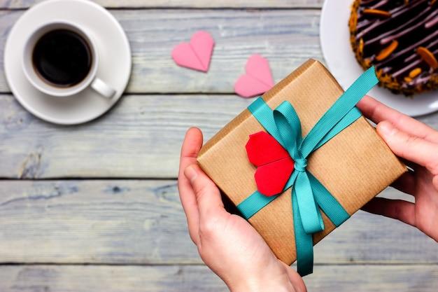 Mãos femininas dão um presente embrulhado em papel artesanal.