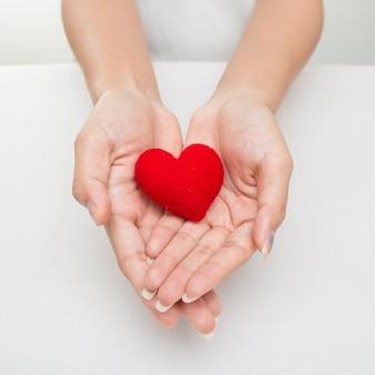 Mãos femininas, dar, coração vermelho