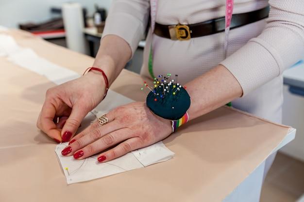 Mãos femininas de alfaiate com tecido, estampa e agulha na oficina