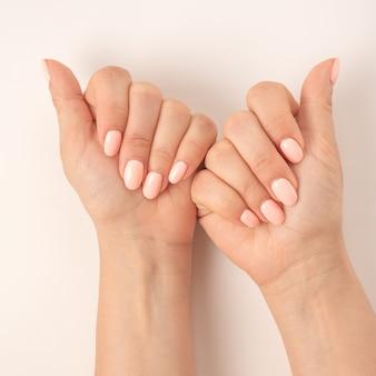 Mãos femininas de close-up com uma bela manicure em fundo branco. mostra a vista superior da mulher safra, demonstrando as mãos com manicure elegante e elegante. imagem quadrada