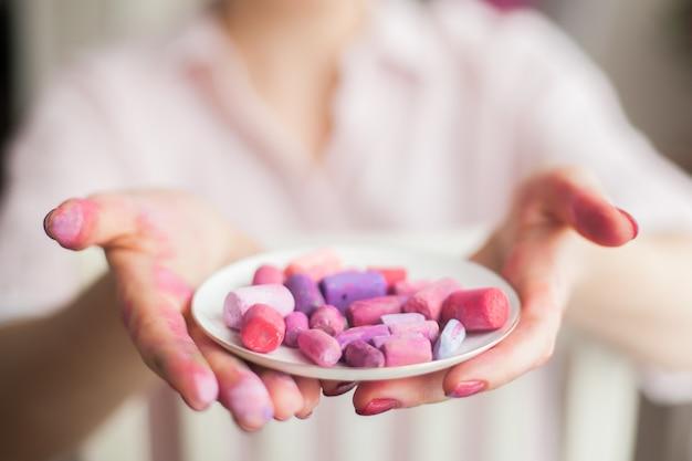 Mãos femininas de close-up de vista superior borradas em tinta roxa seguram e um prato com um pastel seco de tons quentes de lilás rosa e roxo. conceito de trabalho criativo do studio