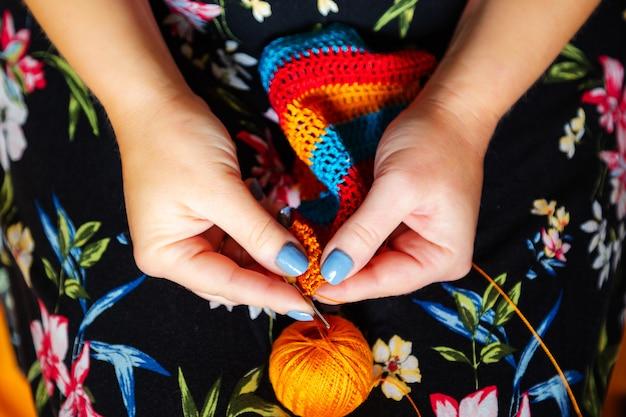 Mãos femininas de crochê.