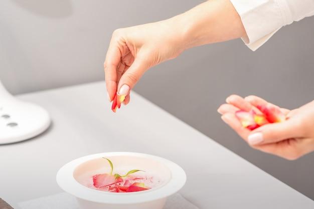 Mãos femininas de esteticistas preparando o banho de manicure com pétalas de rosas vermelhas e rosa na mesa do spa