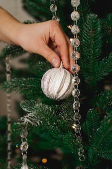 Mãos femininas decorando a árvore de natal verde com bolas de prata.