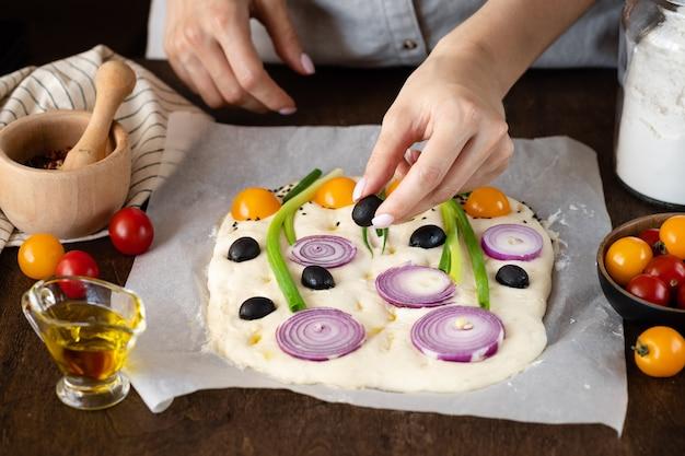 Mãos femininas decorando a massa de focaccia crua com legumes. focaccia de arte de flor caseira. vista lateral