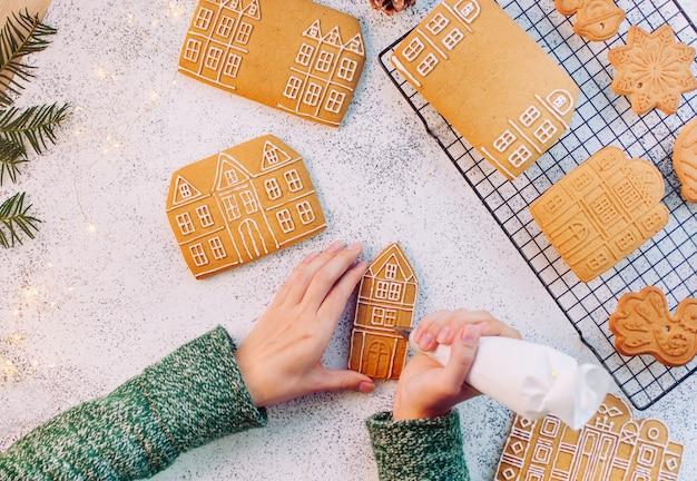 Mãos femininas decorando as casas de biscoitos de gengibre de natal. vista superior, configuração plana.