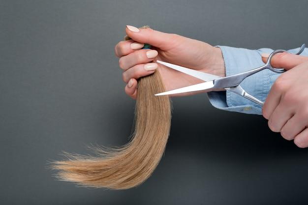 Mãos femininas demonstram tesoura e cabelo cortado