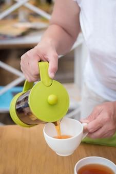 Mãos femininas, despejando um chá para cima