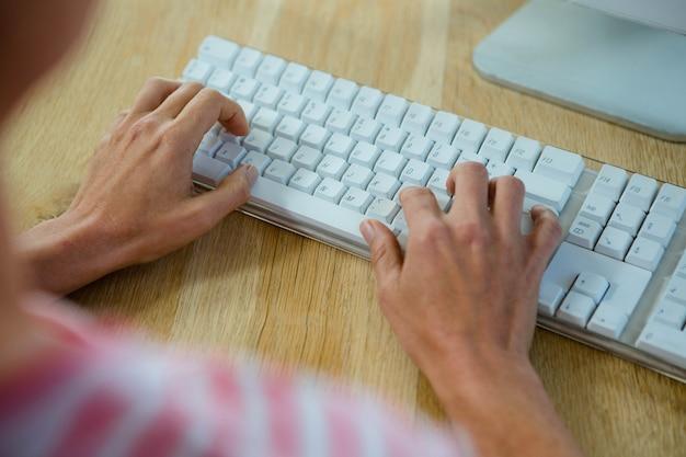 Mãos femininas digitando em um teclado, em uma mesa