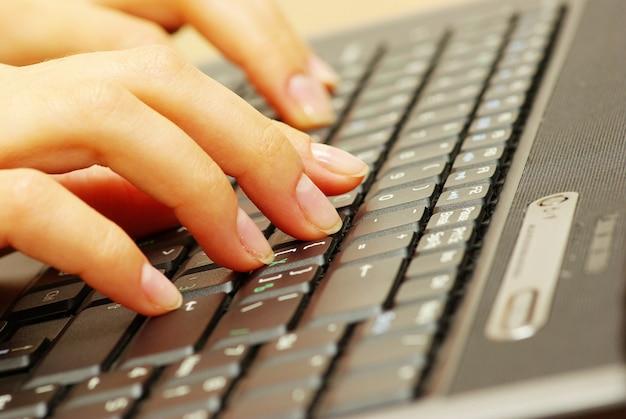 Mãos femininas digitando no teclado do laptop