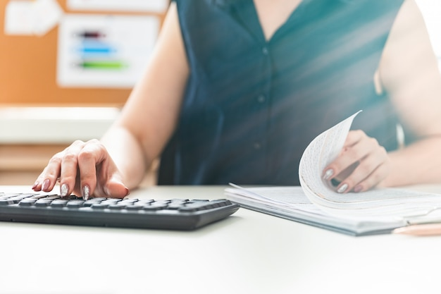 Mãos femininas digitando no teclado e folheando os documentos.