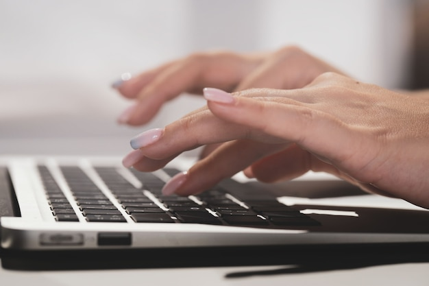 Mãos femininas digitando texto em um laptop